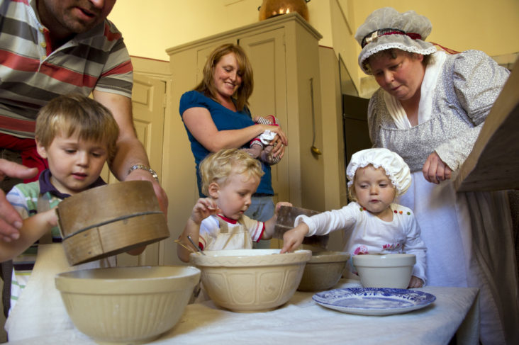 Costumed interpreter with visitors in the Kitchen at Attingham Park, Shropshire. National Trust